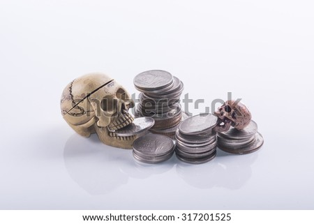 isolated of human skulls eating coins, idea for saving and financial