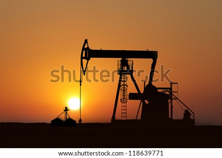 isolated oil pump in action at sunset - stock photo