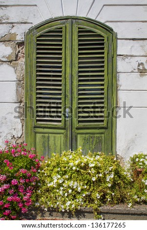 Isolated old colonial mansion door with flowers in front - stock photo