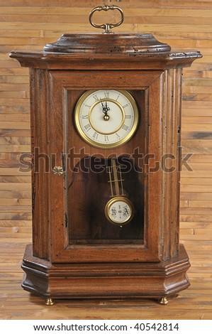 isolated old-fashion wooden clock with pendulum on bamboo background - stock photo