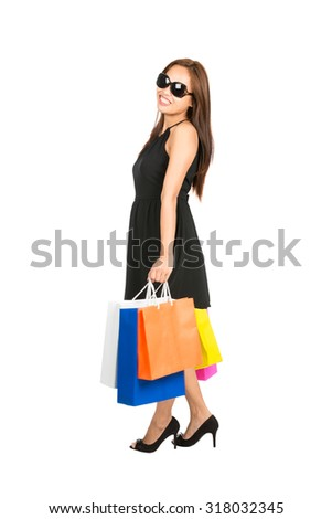 Isolated on white background profile of an attractive female shopper casually standing around wearing a stylish black dress and sunglasses holding colorful shopping bags. Full length - stock photo