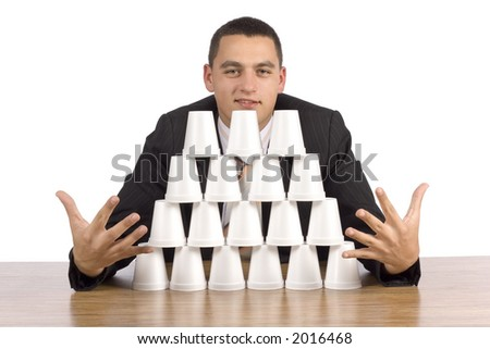 isolated on white businessman building cups' pyramid - stock photo