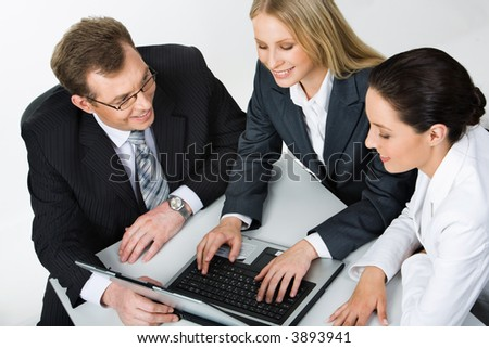 Isolated on white portrait of businesswoman sitting at the table typing on the laptop and two people sitting near by her looking at the monitor of laptop