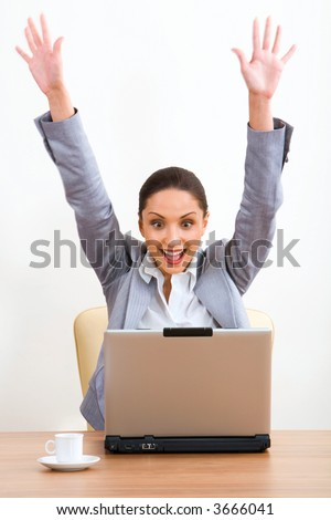 Isolated on white portrait of happy brunette businesswoman with raised hands sitting at the table with the opened laptop and a cup on it - stock photo