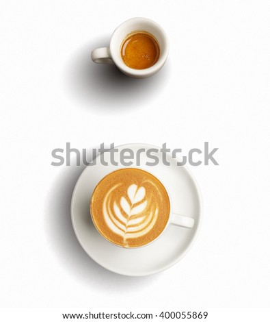 Isolated on white set of two ceramic cups with aromatic freshly brewed espresso or ristretto and cappuccino with milky foam art on top in tree shape - stock photo