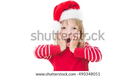 isolated on white small blond girl in santa claus hat looking surprised, holding hands next to face with open mouth