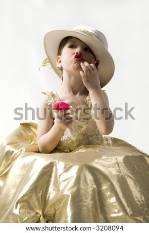 Isolated on white sweet brunette little girl in light goldish dress and white hat making up her lips - stock photo