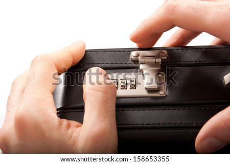 Isolated on white these masculine hands are trying to unlock the combination lock on the briefcase. - stock photo