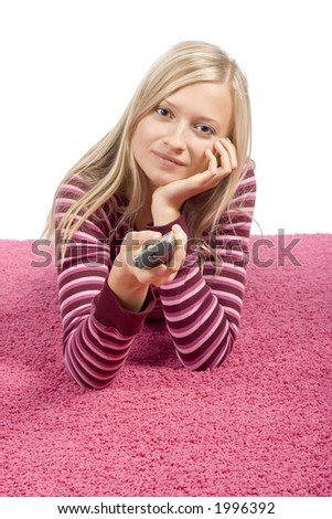 isolated on white young blonde woman lying on the pink carpet with remote control - stock photo