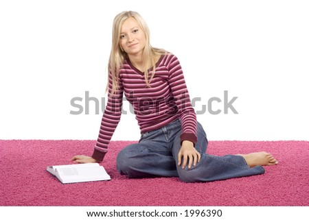 isolated on white young blonde woman sitting on the pink carpet with book - stock photo