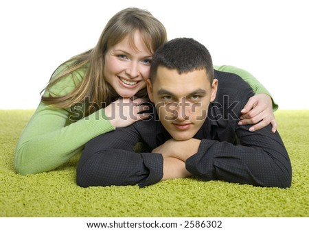 isolated on white young couple lying on the green carpet - stock photo