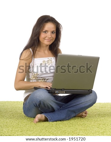 isolated on white young woman with laptop on the green carpet - stock photo