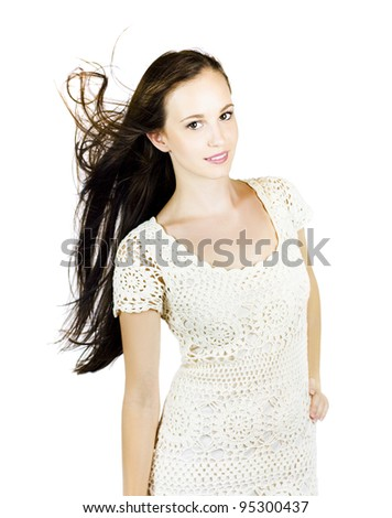 Isolated Over White Photograph Of A Stunning Brunette Woman Standing Confidently With Hair Blowing In The Wind During A Glamour Fashion Model Photoshoot - stock photo