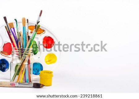 isolated paints brushes in a glass and yellow water paint - stock photo