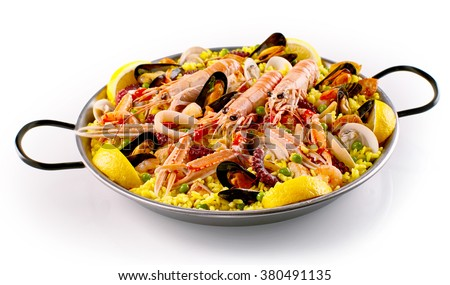 Isolated pan full of cooked large shrimp, yellow rice, clams and green peas with lemon wedges over white background - stock photo