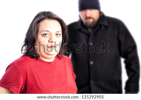 Isolated photo of a woman in red shirt being assaulted from behind by a white male in a black coat, hat and gloves. The man is blurred out of focus behind the woman