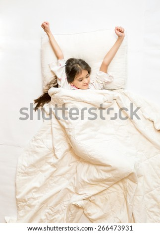 Isolated photo of cute girl being awake and stretching in bed - stock photo