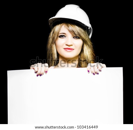 Isolated photograph of a female architect wearing hard hat while holding a blank white sign in hands in a design your own property blueprint with copyspace - stock photo