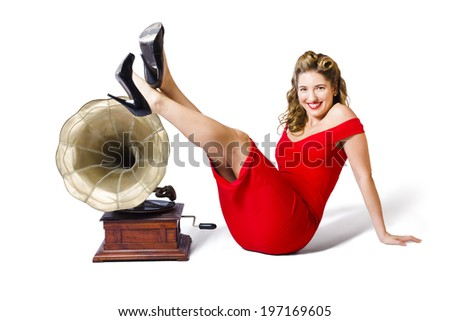 Isolated photograph of a pretty and young pinup girl in rockabilly dress kicking up a pose next to antique record player in a musical depiction of classical music - stock photo