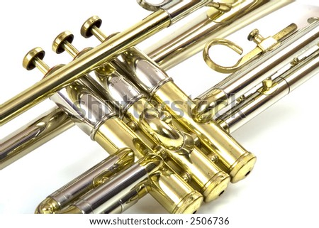 Isolated photograph of the middle section (valves) of a silver and brass trumpet.
