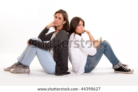 Isolated picture of an angry mother back to back with her teenage daughter - stock photo