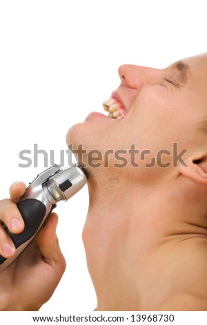 Isolated pictures in studio. Portrait young the man is happy and has a shave with the electro razor. - stock photo