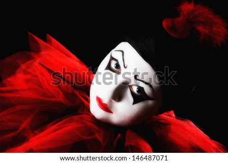 Isolated Pierrot against a black background with a vibrant red collar - stock photo