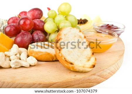 Isolated platter of assorted fruit and cheese - stock photo