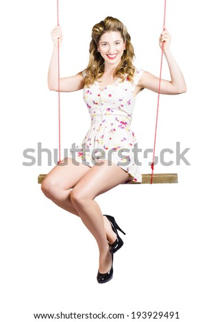 Isolated portrait of a beautiful fifties pin up girl playing on makeshift swing on white background - stock photo