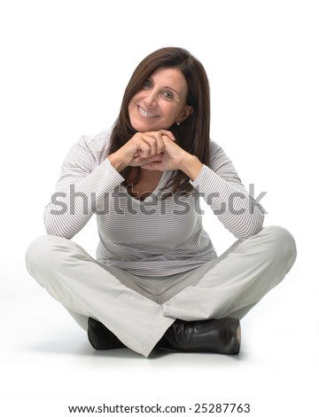 Isolated portrait of a beautiful smiling woman sitting on the floor with her legs crossed - stock photo