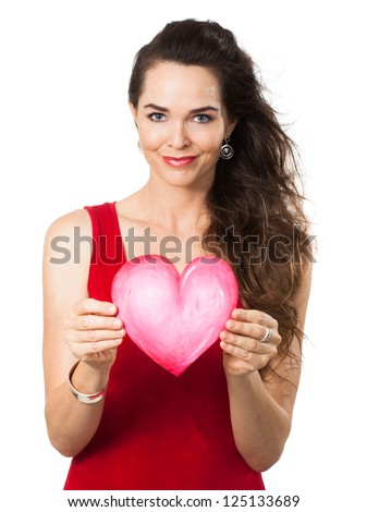 Isolated portrait of a beautiful young woman in a red dress holding a red love heart. - stock photo