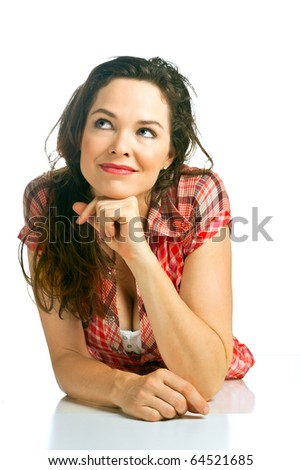 Isolated portrait of a beautiful young woman lying on the floor looking contemplative - stock photo