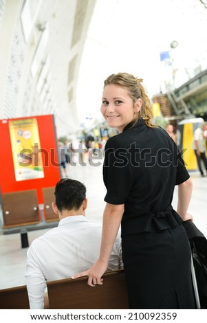 isolated portrait of a cheerful young business woman in a public station - stock photo