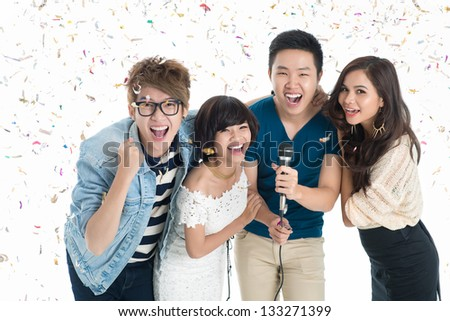 Isolated portrait of a group of friends throwing a party with serpentine falling all around them - stock photo