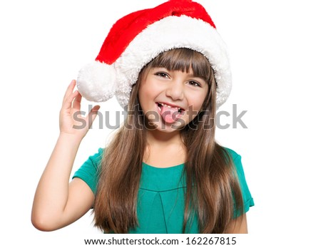 Isolated portrait of a little girl in a Christmas hat that shows the tongue
