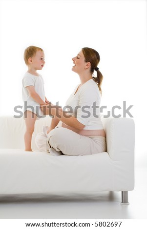 Isolated portrait of a pregnant young mother sitting cross-legged on a couch with her toddler child standing next to her...Predominantly white. - stock photo