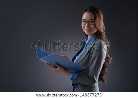 Isolated portrait of a young business lady posing at camera over a grey background - stock photo