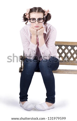 Isolated portrait of a young depressed nerdy girl sitting alone on park bench - stock photo