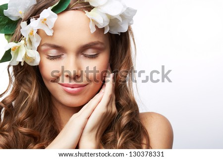 Isolated portrait of a young perfect woman with hair decorated with flowers - stock photo