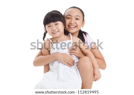 Isolated portrait of two cute sisters cuddling in front of the cam - stock photo