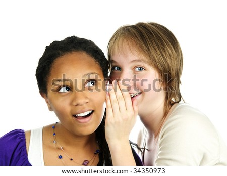 Isolated portrait of two diverse teenage girl friends whispering - stock photo