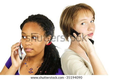 Isolated portrait of two teenage girls with cell phones - stock photo