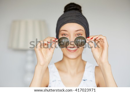 Isolated portrait of young female holding round shades that she just bought during shopping. Attractive woman looking at the camera with cheerful expression, enjoying her new trendy sunglasses  - stock photo