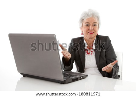 Isolated quizzically older senior woman working with computer on white.  - stock photo