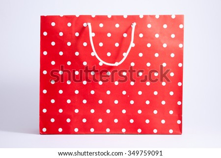 Isolated red polka dot paper shopping bag on white background
