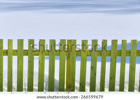 isolated rustic fence on the white snow in winter - stock photo