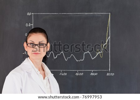 Isolated scientist standing near the blackboard and looking at the camera - stock photo