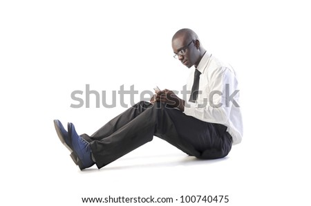 Isolated seated african businessman using a mobile phone - stock photo
