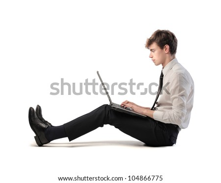 Isolated seated young businessman using a laptop - stock photo