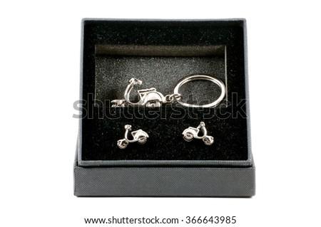 Isolated set of keychain motorbike and cufflinks over white - stock photo